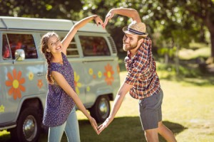 36406325 - hipster couple making heart with arms on a summers day