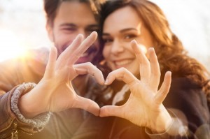 38774765 - closeup of couple making heart shape with hands