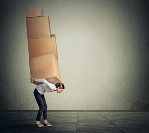 43388475 - girl holding carrying several boxes on her back in equilibrium