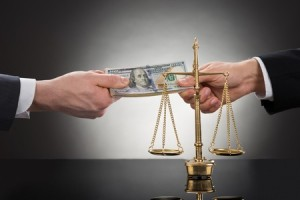 40579635 - close-up of a businessman taking bribe in front of justice scale